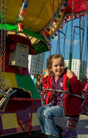child riding on a fairground with a whirligig and has fun