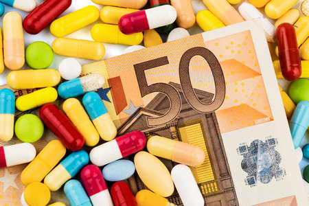 euro notes and tablets, symbol photo for costs of drugs and health insurance.