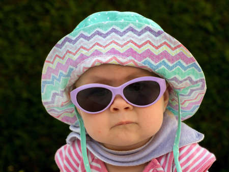 Photo pour a baby with sunglasses and sun hat is well equipped against the heat in summer - image libre de droit