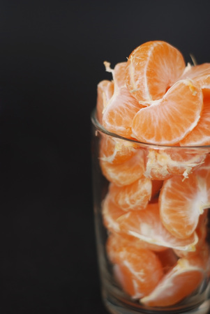 Fresh Peeled Tangerines Divided into Slices on Glass Cup. Properties of Mandarins for Health Concept on Black Background. Vertical Image.