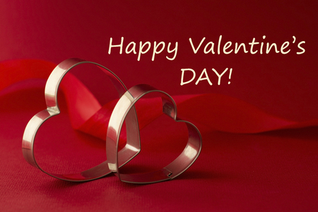 Foto de Happy Valentine's Day inscription. Greeting card. Two red heart shaped cookie cutters on beautiful red background. - Imagen libre de derechos