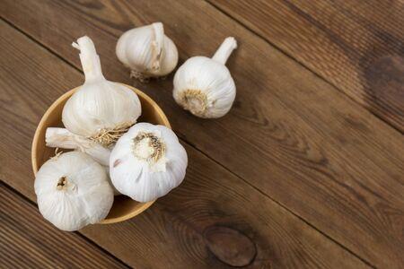 Foto für Isolated garlic whole on wooden background. Cooking ingredients, copy space - Lizenzfreies Bild