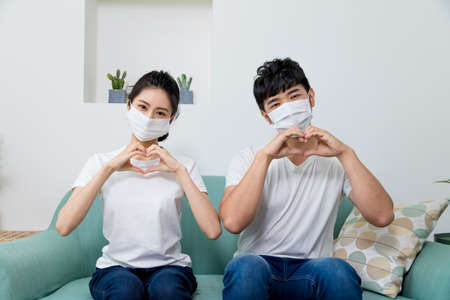 Photo pour Asian couple wearing protective face mask and making shape of Heart by their Hands at home. - image libre de droit