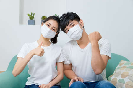 Photo pour Asian couple wearing protective face mask and showing thumb up at home. - image libre de droit