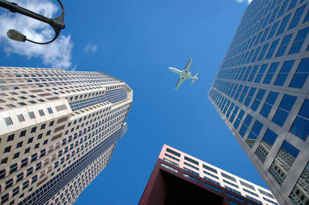 Corporate jet flying high above business district.