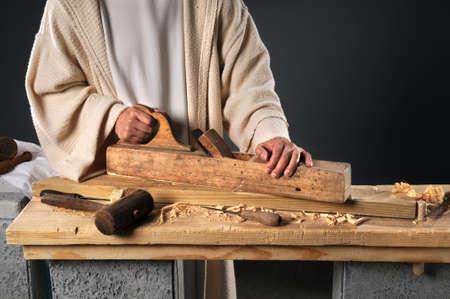 Photo pour Jesus working with wood plane in carpenter's workshop - image libre de droit