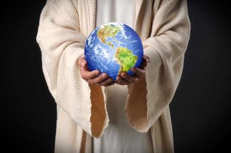 Hands of Jesus holding world in hands over dark background