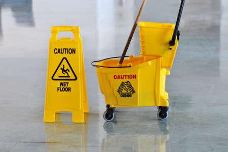 Mop bucket and caution sign on wet floor