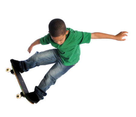 Young African American boy performing trick with skate board isolated over white