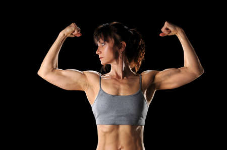 Mature woman flexing muscles isolated over black background