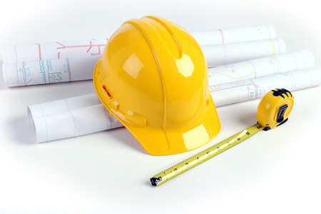 Architectural plans, hardhat and measuring tape over white table