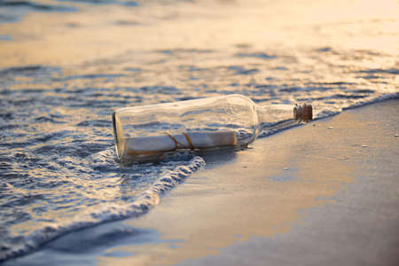Message in a bottle on beach during sunset
