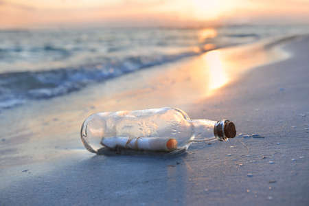 Message in a bottle resting on shore during sunset