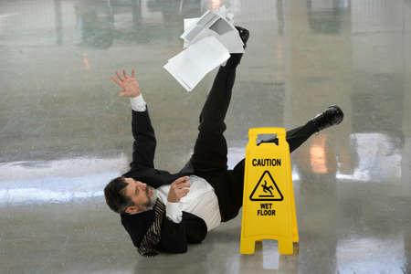 Photo pour Senior businessman falling on wet floor in front of caution sign - image libre de droit