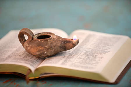 Ancient Israelite oil lamp on open Bible over vintage table