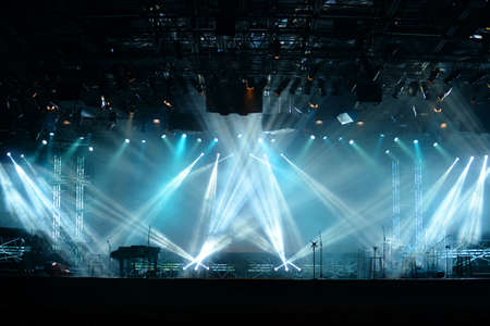 Lights beams on stage with piano and musical instruments
