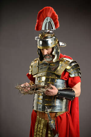 Roman soldier holding crown of thorns over neutral background