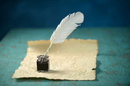 Writing Inkwell with feather and vintage paper on table