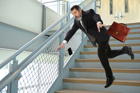 Photo pour Senior Hispanic businessman falling on stairs - image libre de droit