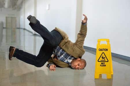African American businessman falling on wet floor in office