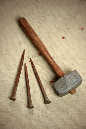 Ancient metal nails and hammer over vintage cloth with blood drops