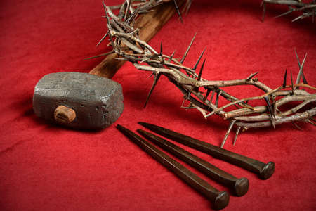 Crown of thorns, nails and hammer representing crucifixion symbols on red cloth