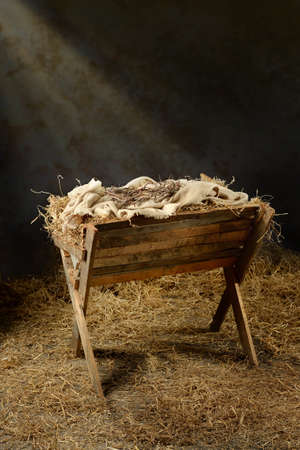 Foto de Manger with crown of thorns in barn with light coming from above - Imagen libre de derechos