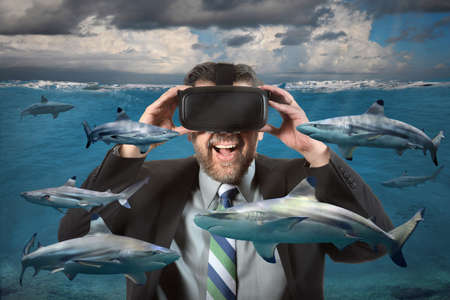 Photo pour Businessman seeing sharks in the ocean using virtual reality glasses - image libre de droit
