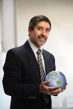 Portrait of Hispanic businessman holding earth in his hands inside office buildingの写真素材