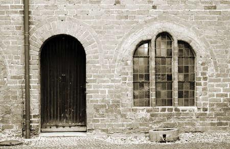 The photograph of the facade of an old farm, a brick building