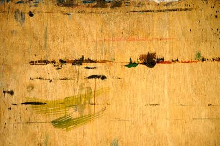 Eine abstrakte und mit Farbe bekleckste Spanplatte, das Malutensil eines Malers.