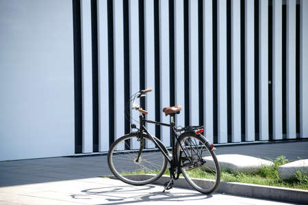An old bicycle stands in front of the facade of a modern building.
