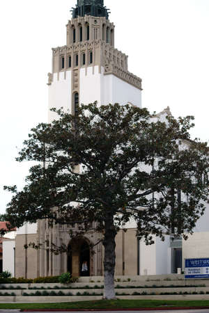 Los Angeles, United States - December 27, 2015: The entrance and tower of Westwood UMC church with a tree and flower beds in front of its white facade on December 27, 2015 in Los Angeles.