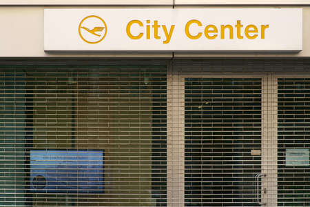 Photo for Frankfurt, Germany - July 06, 2019: The logo of the travel agency Lufthansa City Center over the barred shop window of a closed shop on 06 July 2019 in Frankfurt. - Royalty Free Image