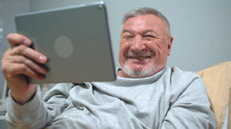 Man lie on the bed in the hospital and talk with someone on tablet