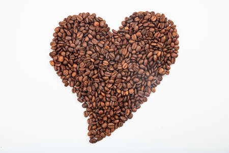 Heart made from coffee beans on white background