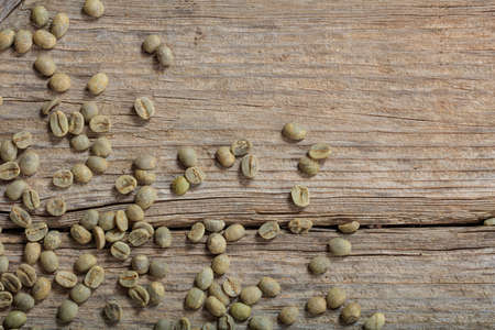 Green coffee beans on wooden background