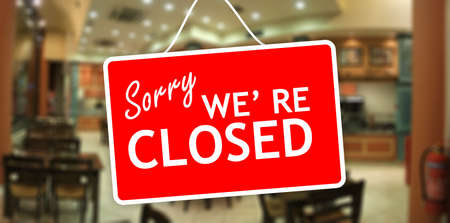 Photo for Sorry we are closed sign hanging on a glass storefront - Royalty Free Image
