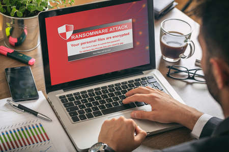 Foto de Ransomware alert message on a laptop screen - man at work - Imagen libre de derechos