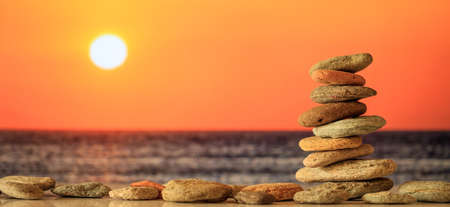 Foto de Zen stones stacked on sea background at sunset - Imagen libre de derechos