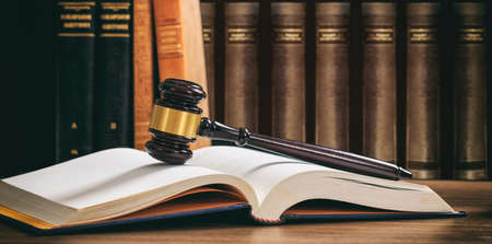 Photo pour Law gavel on an open book, wooden desk, law books background - image libre de droit