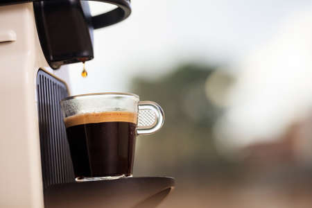 Making espresso. Espresso coffee maker on a blurred background, space for text