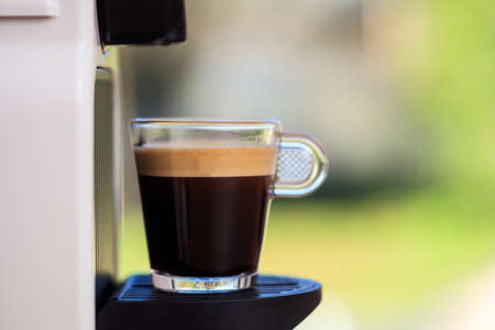 Making espresso. Espresso coffee maker on a blurred background, space for text, front view