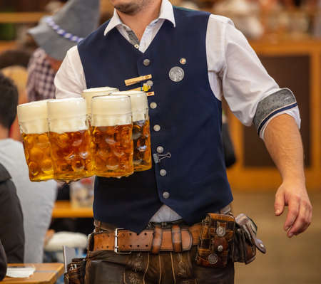 Foto per Oktoberfest, Munich, Germany. Waiter with traditional costume serving beers, closeup view - Immagine Royalty Free