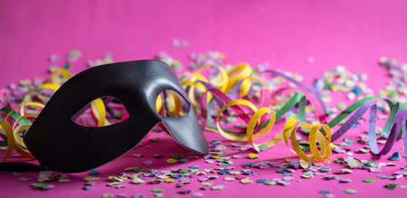 Foto de Carnival party. Black mask, streamers and confetti on bright pink background, banner - Imagen libre de derechos