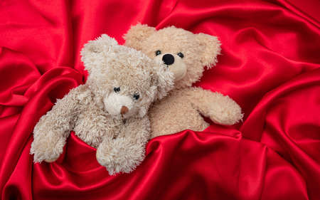 Foto de Love, valentines day concept, tight hug. Two teddy bears embracing as a couple in bed, red satin background - Imagen libre de derechos