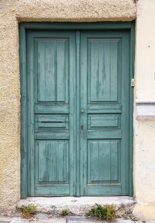 Foto de Wooden worn and faded green door, closed house entrance. Traditional building facade, old town of Plaka, Athens Greece - Imagen libre de derechos