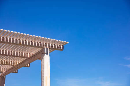 Foto de White wooden pergola for sun protection, clear blue sky background, copy space, closeup view - Imagen libre de derechos