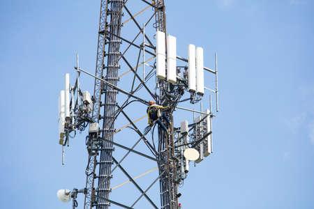 Photo pour Communication maintenance works. Technician climbing on telecom tower antenna against blue sky background, copy space. - image libre de droit