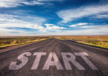 Start, new beginning concept. Text sign on a long straight highway in the american desert, blue cloudy sky background
